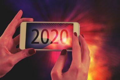 2020年と書かれたスマホをもつ女性