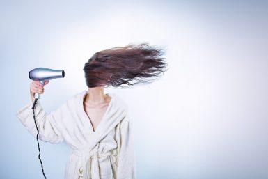 ドライヤーで髪を横からかわかして顔がまったくみえない風呂上りの女性