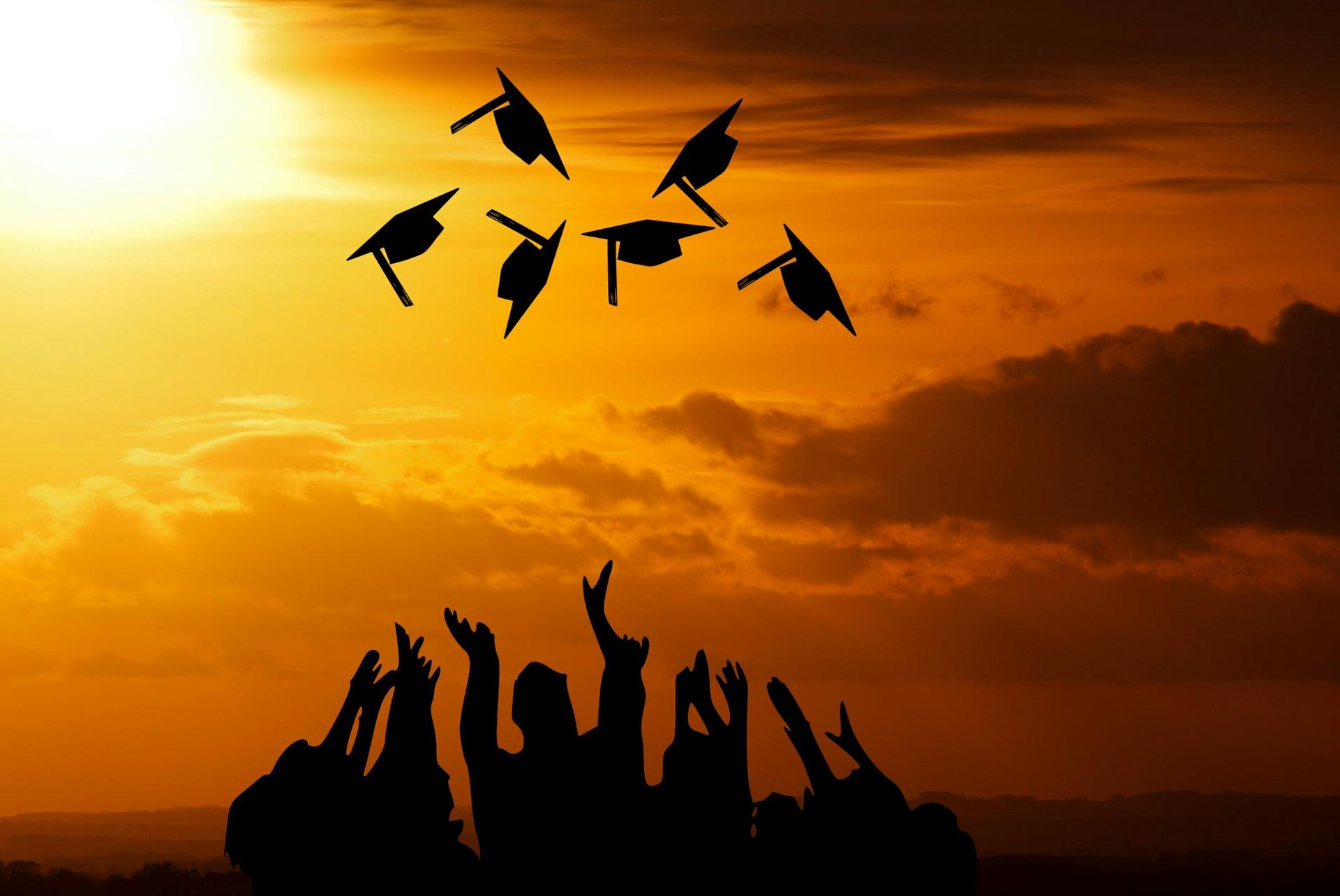 学問の帽子を複数、天に向かって投げる学生たち