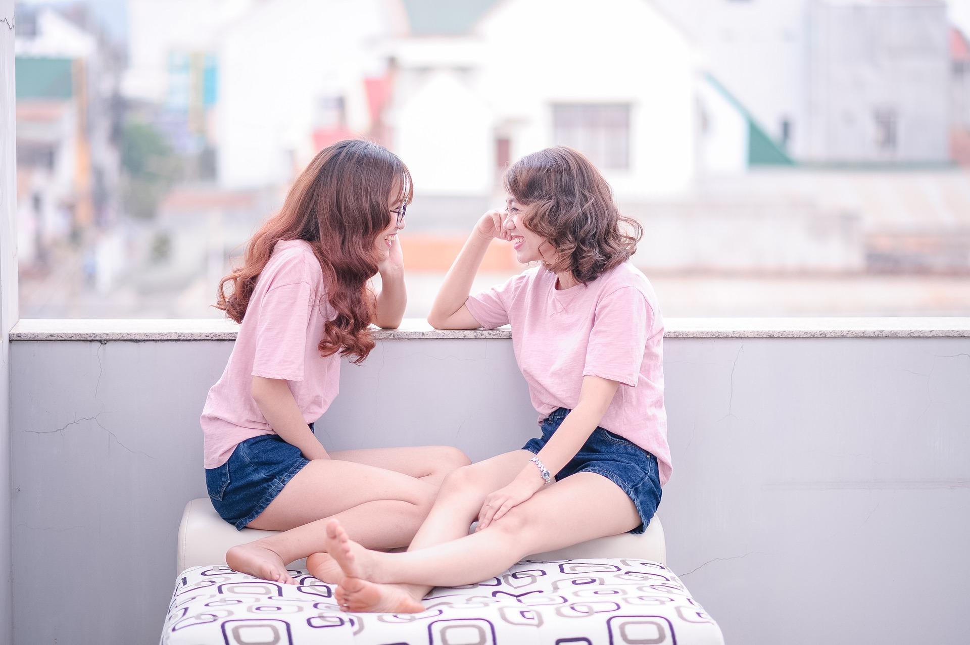 ゴシップを話す2人のピンクの服をきた女性
